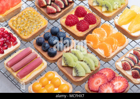 Bunte square Obstkuchen auf einem Gitter vor einem weißen Hintergrund