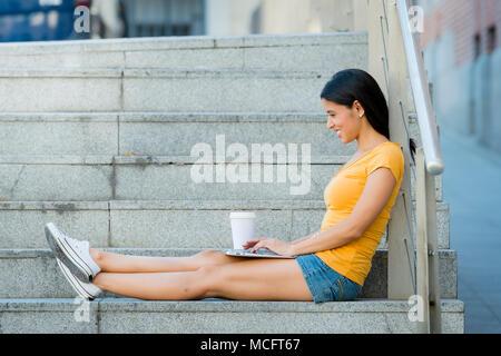 junge attraktive Latin Frau in trendige Freizeitkleidung studieren oder arbeiten auf Laptop-Computer im städtischen Hintergrund der europäischen Stadt - Stockfoto