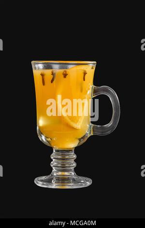 Einfarbige blickdichte Cocktail, gelb Glühwein in einem hohen Glas mit einem Griff mit Gewürzen und einer Scheibe Zitrone, Orange. Von der Seite. Isolierte schwarze backgr - Stockfoto