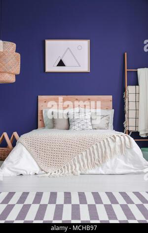 ... Poster Auf Lila Wand über Dem Bett Mit Hölzernen Bedhead Und Stricken  Decke In Gemütlichen Schlafzimmer