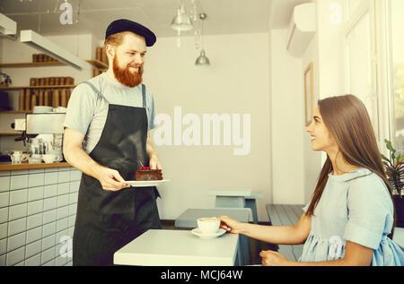 Kaffee Geschäftskonzept - Kellner oder Barkeeper, Schokoladenkuchen und sprechen mit kaukasischen schöne Dame in blauem Kleid im Coffee Shop. - Stockfoto