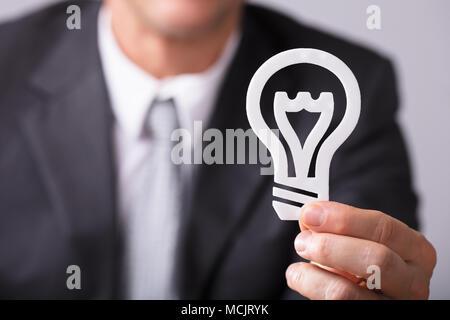 Nahaufnahme der Kaufmann Hand Weiße Glühbirne - Stockfoto