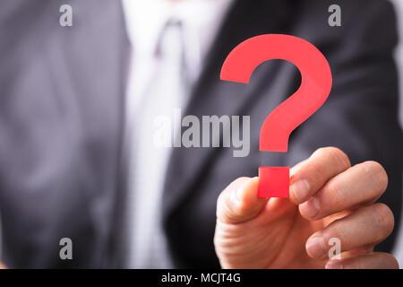 Nahaufnahme der Kaufmann Hand halten roten Fragezeichen Zeichen - Stockfoto