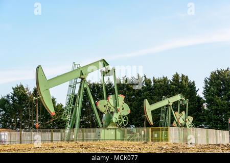 Zwei aktive pumpjacks Öl pumpen aus einer gut befindet sich im Zentrum von Frankreich unter einem blauen Himmel. - Stockfoto