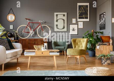 ... Kunst Sammlung Auf Eine Graue Wand, Holz  Couchtisch, Sessel Und Rote  Rad In