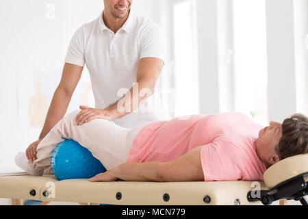 Lächelnd Therapeuten Massieren eine alte Frau mit Osteoporose über eine blaue Kugel - Stockfoto