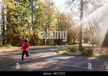 Läuferin Joggen auf der Straße in der Nähe des Lake Washington, Seattle, Washington State, USA - Stockfoto