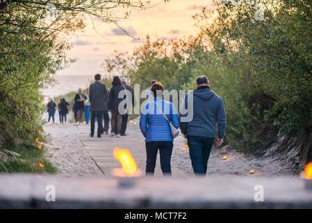 Romantische Lagerfeuer Nacht am Meer bei Sonnenuntergang. Leute versammeln um Nacht der alten Leuchten feiern. Wandern auf Holz weg am Meer - Stockfoto