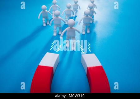Ansicht der Horseshoe Magnet für menschliche Figuren isoliert auf blauem Hintergrund - Stockfoto