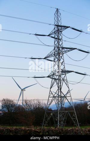 Windenergieanlagen beleuchtet in der Abendsonne neben einem traditionellen Strom Strommast und Leitungen in der Nähe von Gretna, Dumfries und Galloway. - Stockfoto