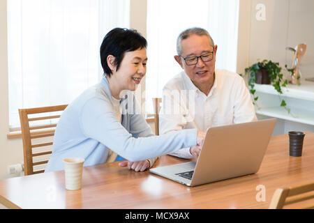 Älteres Paar mit Laptop zusammen - Stockfoto