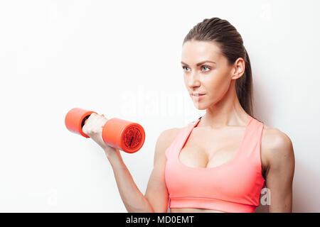 Seite Ansicht Porträt eine hübsche junge Sportlerin, die Übungen mit Hanteln isoliert auf weißem Hintergrund - Stockfoto