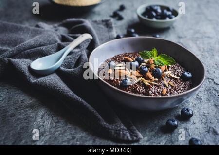 Gesunde Schokolade Quinoa Porridge mit Kokosmilch, Honig, Mandeln und blueberry - Stockfoto