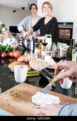 Vorbereitung fetta Käse. Gruppe von Freunden beiläufig Snacking auf eine Auswahl von Lebensmitteln beim Lachen und sich zu amüsieren. - Stockfoto