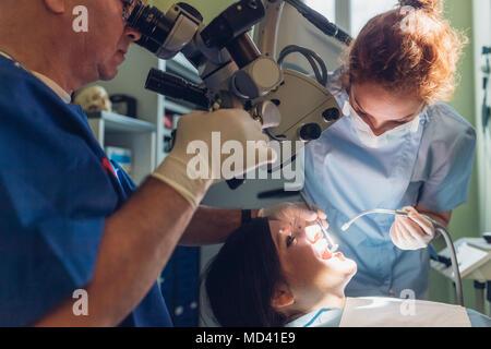 Zahnarzt und zahnmedizinische Krankenschwester, die zahnmedizinischen Verfahren auf weibliche Patienten - Stockfoto