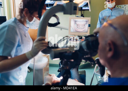 Zahnarzt und zahnmedizinische Krankenschwester Durchführung Vorgehensweise am Patienten - Stockfoto