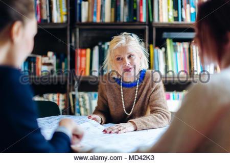 Drei Geschäftsfrauen, sitzen um den Tisch, durch Dokumente - Stockfoto