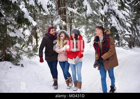 Freunde wandern und Lachen im Schnee - Stockfoto