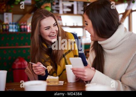 Junge Frauen lächelnd über SMS auf Handy - Stockfoto