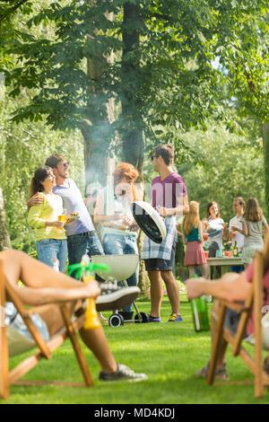 Grill Party in einem Park von einer großen Gruppe von Freunden genießen das warme Wetter und Essen statt