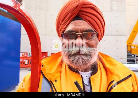 Ein Sikh Crossrail Arbeiter mit harten Hut Freistellung in hohe Sichtbarkeit Arbeit tragen vor Ort im Zentrum von London. - Stockfoto