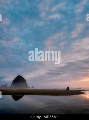 Cannon Beach bei Sonnenuntergang mit Haystack Rock, Bach und Paar mit Hund. Oregon - Stockfoto