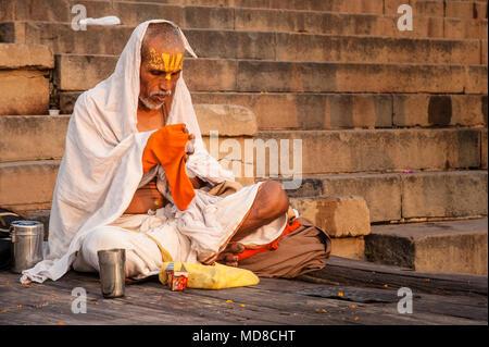 Ein Hindu Mann sitzt im Gebet vor der Ganges, auf der ghats in Varanasi - Stockfoto