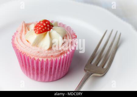 Rosa Erdbeere Cupcake auf weißer Teller mit Gabel - Stockfoto