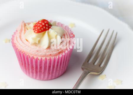 Rosa Erdbeere Cupcake auf weiße Platte mit Stern besprüht - Stockfoto