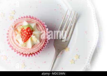Rosa Erdbeere Cupcake auf weiße Platte mit Stern besprüht, Overhead - Stockfoto