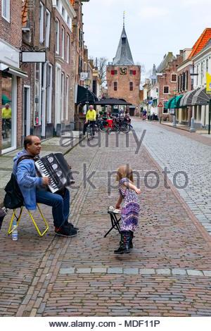Ein junges Mädchen gibt eine Münze zu einem Straßenmusiker spielen seiner Ziehharmonika auf Jufferenstraat in der alten Hansestadt Elburg, Niederlande. - Stockfoto