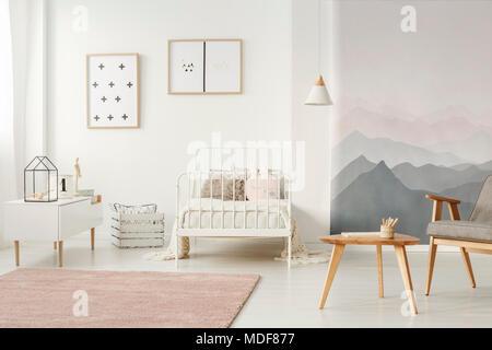 Weiß, Metall Bett stand in hellen Kinder Zimmer Einrichtung mit einfachen Poster, schmutzig rosa Teppich und Tapeten - Stockfoto