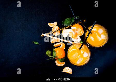 Erfrischender Cocktail mit Mandarinen, Saft und Eis in zwei Gläser auf einem schwarzen Hintergrund, alkoholische Getränke, Kopie Raum - Stockfoto