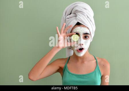 Junges Mädchen mit einer Gesichtsmaske auf Holding eine Gurke in Scheiben schneiden vor einem Auge - Stockfoto