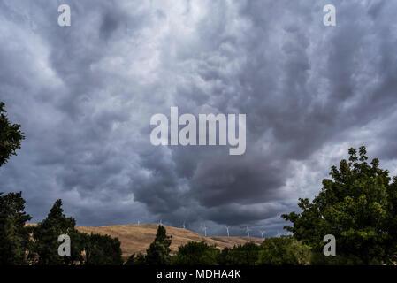 Dunkle Wolken Webstuhl über Klickitat County mit Windkraftanlagen auf den Hügeln; Maryhill, Washington, Vereinigte Staaten von Amerika - Stockfoto