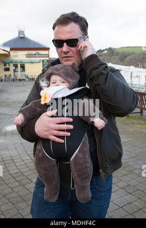 Vater Baby in Schlinge während auf dem Telefon - Stockfoto