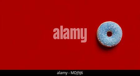 Blau Donut mit mit Kokosraspeln auf einem roten Hintergrund. - Stockfoto
