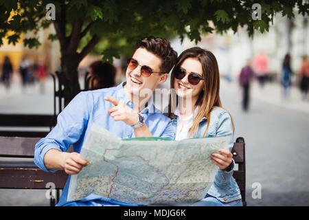 Junges Paar mit Karte verweist auf ein Wahrzeichen Backpackers in der Stadt - Stockfoto