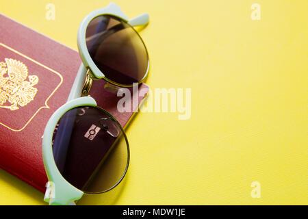 Sonnenbrille einen russischen Pass auf gelbem Hintergrund Vorbereitung für die Reise. - Stockfoto