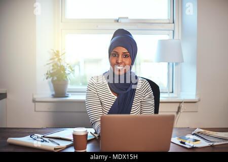 Junge arabische weibliche Unternehmer Tragen eines hijab selbstbewusst lächelnd während der Arbeit auf einem Laptop in Ihrem home office - Stockfoto