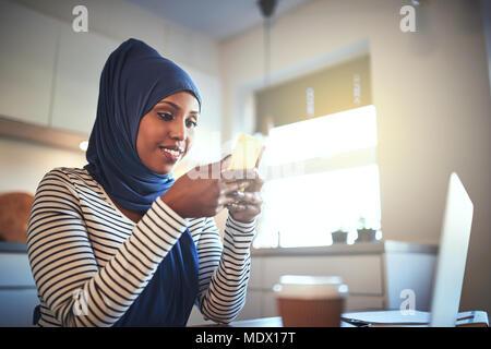 Lächelnden jungen arabischen Frau trägt ein Kopftuch sitzen in ihrer Küche zu Hause eine Textnachricht senden und über einen Laptop - Stockfoto