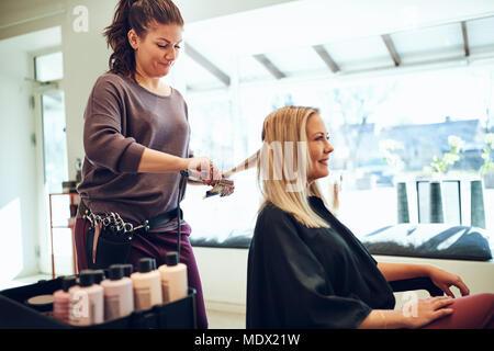 Lächelnde blonde junge Frau sitzt in einem Salon Stuhl in ihr Haar gerichtet, indem ihr Hairstylist - Stockfoto