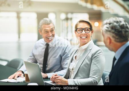 Gruppe der lächelnde ältere Kollegen sitzen zusammen in einem Büro Tisch diskutieren Arbeit während einer Konferenz - Stockfoto