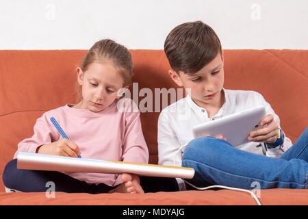 Zwei Kinder spielen, eins mit dem malbuch und der andere mit der digitalen Tablet - Stockfoto