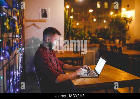 Eine junge Stattlichen kaukasischen Mann mit Bart und toothy Lächeln in einem rot kariertem Hemd ist die Arbeit hinter einem grauen Laptop an einem Holztisch sitzen. Hände o - Stockfoto