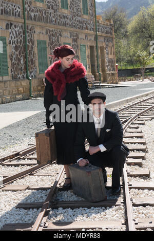 Junges Paar mit Vintage Koffer in tiefe Gedanken Standortwahl auf der trainlines für Trennung und eine Reise bereit. - Stockfoto