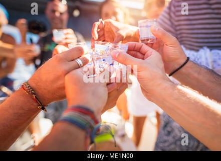 Nahaufnahme eines Menschen Hände mit Glas voll des alkoholischen Getränks, Toast, Cheers, feiern Urlaub, Open Air Party, happy Sommer Urlaub