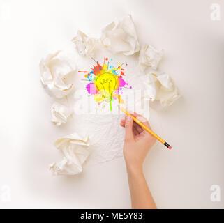 Weibliche Hand neben ein paar zerknittertes Papier Kugeln zeichnen ein farbenfrohes Glühbirne - Stockfoto