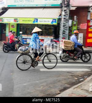 Eine weibliche Radfahrer tragen eine kegelförmige Hut reiten ihr Fahrrad neben Motorrädern in Ho Chi Minh City, Vietnam. - Stockfoto