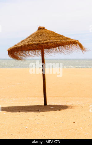 Stroh Sonnenschirm am Sandstrand. - Stockfoto